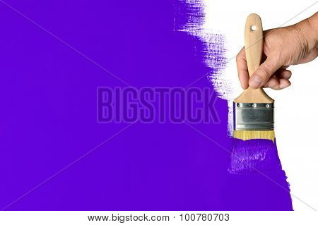 Man's hand using paintbrush with purple paint on wall