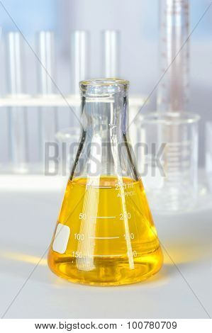 Beaker with yellow colorant on laboratory table