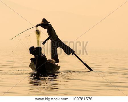 Inle Lake Myanmar - Traditional Burmese Fisherman Balancing On The Paddle While Recovering Fishnet