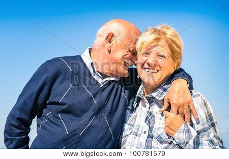 Happy senior couple in love during retirement - Joyful elderly lifestyle with man whispering and smi
