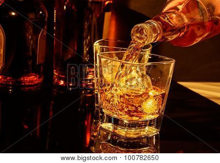Barman Pouring Whiskey In Front Of Whisky Glass And Bottles