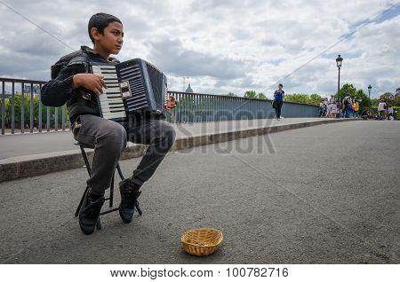Boy plays accordion on Paris bridge