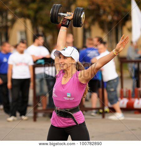 Orel, Russia, September 5, 2015: Slender Girl Weightlifter Lifts Heavy Dumbell With One Hand