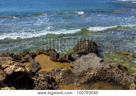 Volcanic Rocks On The Water Edge