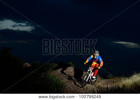 ZAPORIZHZHYA, UKRAINE - JUNE 16, 2015: Fully Equipped Professional Downhill Cyclist Riding the Bike on the Night Rocky Trail. Extreme Sports
