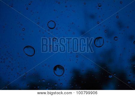 transparent water drops on a bright blue background