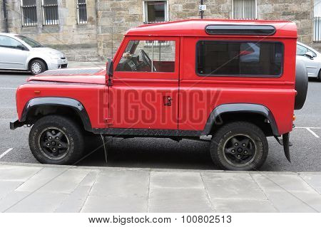 EDINBURGH UK - CIRCA AUGUST 2015: red Land Rover Defender 110 parked on a street in the city centre