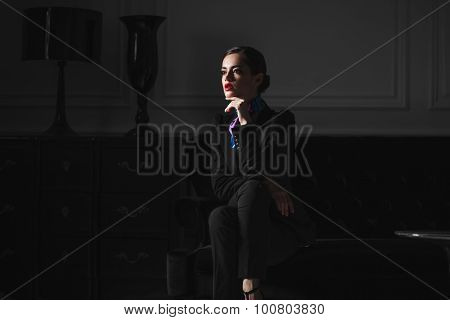 Fashionable Model Woman In Black Suit In Dark Interior