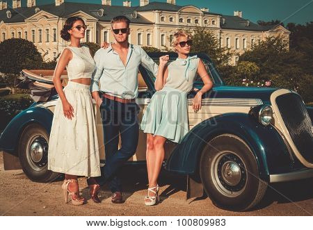 Wealthy friends near classic convertible