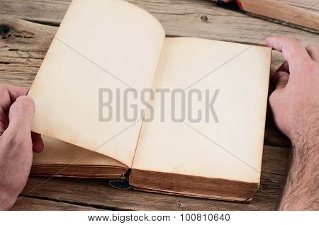 Men Turns The Page Of The Book On The Wooden Table