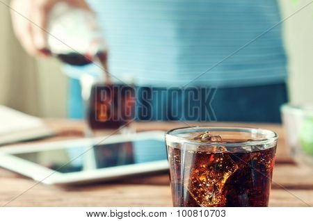 In The Foreground Poured To The Brim Glass Of Cola And Ice Closeup