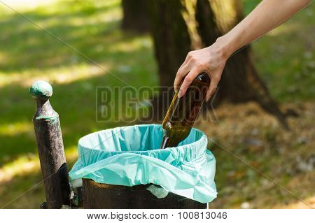 Hand Of Woman Throwing Glass Bottle Into Recycling Bin, Littering Of Environmental