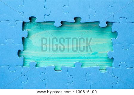 Puzzle Pieces Arranged As A Border Around A Green Wooden Surface