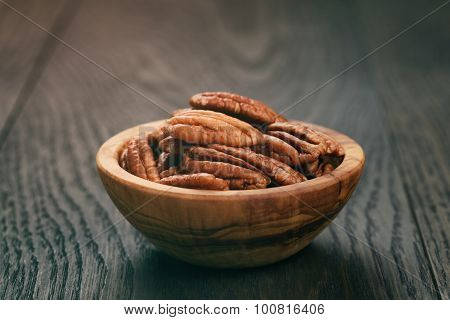 pecan nuts in olive wood bowl on oak table