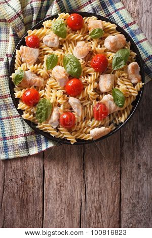 Fusilli Pasta With Chicken, Tomatoes And Basil On A Plate. Vertical Top View