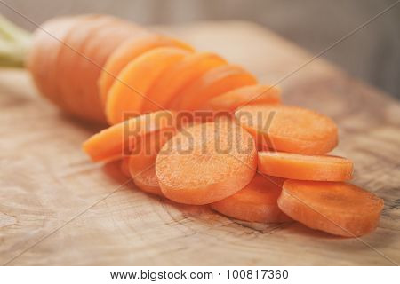 sliced organic carrot on olive wood cutting board closeup photo