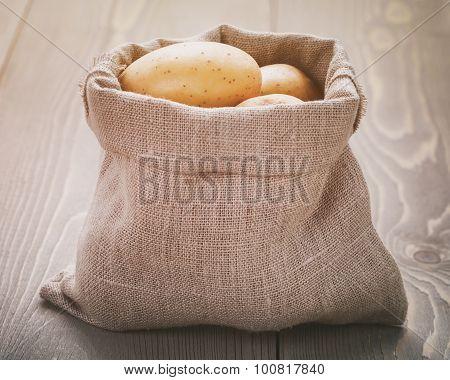 organic raw potato in sack bag on wood table