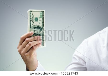 Businessman holding one hundred dollar bills concept for paying, donation, business wealth, venture capitalist and banking