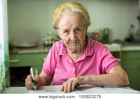Elderly senior woman populates handle her utility bills notices, sitting at the table in the kitchen.