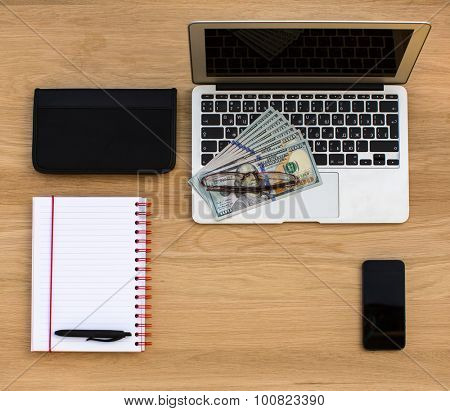 Business card holder, Laptop and hundred dollar bills, Notebook, pen and glasses, lying on oak wood texture, top view.
