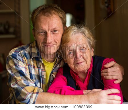 Portrait of old woman with an adult grandson.