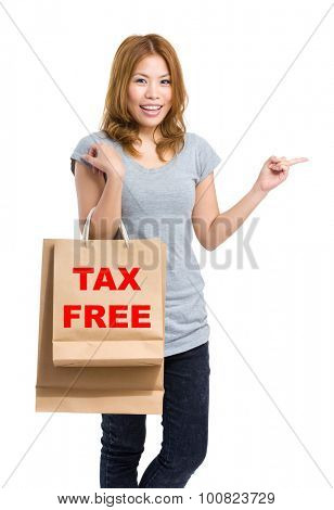 Woman finger point aside and holding shopping bag for showing tax free