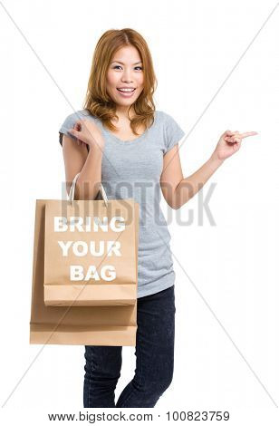 Woman finger point aside and holding shopping bag for showing bring your bag