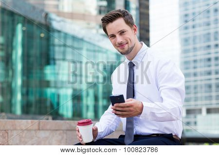 Caucasian young businessman read on the cellphone with coffee