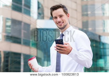 Businessman hold with coffee cup and mobile phone