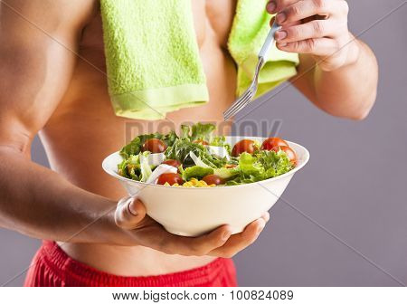 Fit man holding a bowl of fresh salad on grey background