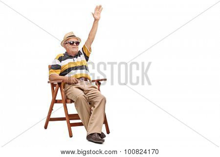 Senior gentleman sitting in a wooden chair and waving to someone with his hand isolated on white background