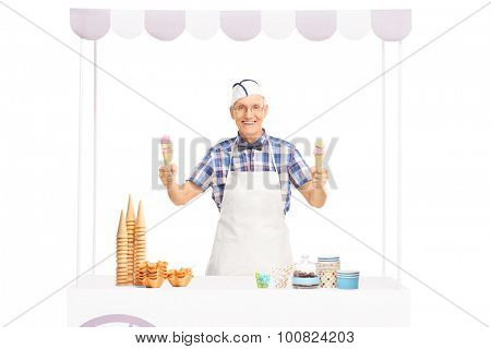 Studio shot of a mature ice cream seller holding two ice cream cones and standing behind a kiosk isolated on white background