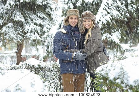 Happy young loving couple embracing in snowfall, smiling, looking at camera.