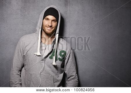 Urban style young man smiling happy, leaning against grey wall, wearing hooded jumper.