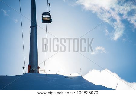 Ski lift or telecabine in a ski resort on a slope, covered with snow during wintersport season, with the sun rising over the mountain