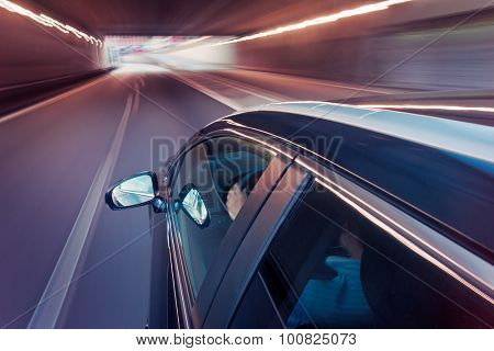 Passenger car, seen from the side of the roof, driving in the middle lane of a motorway, driving through a tunnel