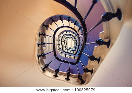 Asymmetric spiral staircase leading up several floors in an old building, looking up.