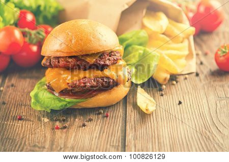 Fresh homemade burger with meat patties served with ketchup sauce with grilled potatoes on wooden table. Cheeseburger close up. Burger with vegetables and French Fries. Vintage rustic style