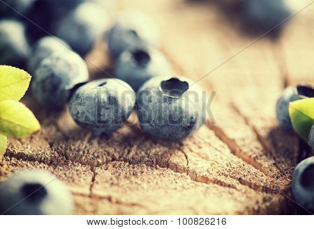 Blueberries close up. Freshly picked testy blueberries over wooden rustic background. Bilberries vintage style. Berries on crack wood