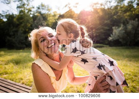 Grandchild kisses grandmother in nature