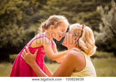 Grandchild and grandmother touching with noses