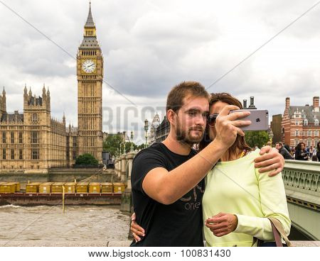 Tourists Taking A Photo Of Big Ben And Houses Of Parliament
