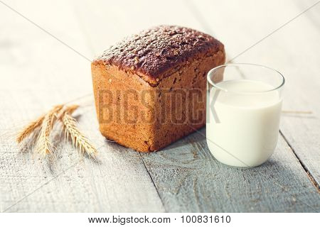 Bread With Milk And Spikelets Of Wheat On A Wooden Boards