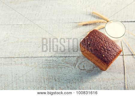 Fresh Bread With Milk And Spikelets Of Wheat On A Wooden Boards.