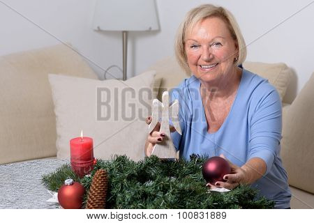 Elderly Lady Holding Up A Christmas Angel