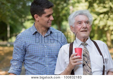 Male Volunteer Supporting Old Man