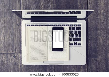 Blank Smartphone On Open Book And Laptop On A Floor, Vintage Photo Effect, Mock Up