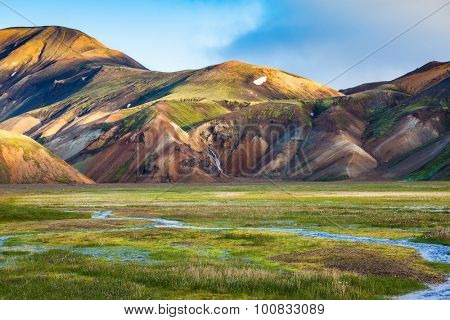 Green Valley is flooded with melt water. Snow lies in the hollows of colorful rhyolite mountains. Early summer morning in the National Park Landmannalaugar, Iceland