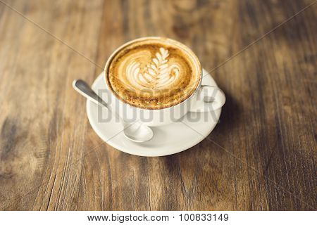 Cup Of Cappuccino And Teaspoon On A Wooden Table