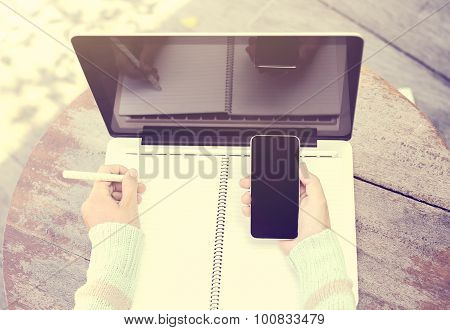 Girl With Smartphone, Blank Diary With Pen And Laptop On A Wooden Table